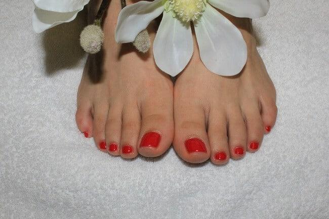 Füße mit roten Fußnägeln nach Fußpflege-Termin